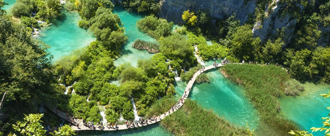 """Tourists go on special tracks around the lake in the park Plitvice Lakes, Croatia. Plitvice Lakes - National Park in Croatia, located in the central part of the country. Since 1979, the national park """"Plitvice Lakes"""" is included in the register of """"World Heritage"""" by UNESCO. Initially, the park was not available to visitors, but were subsequently built wooden walkway and ecological transport running on electricity. Plitvice lakes are very popular among tourists."""